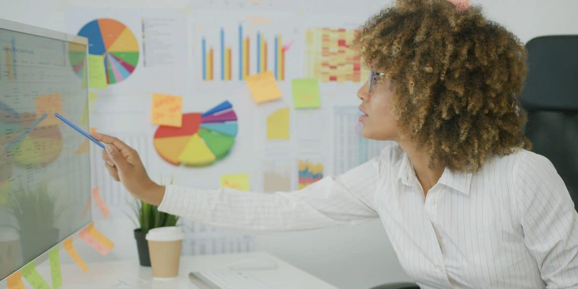 businesswoman surrounded by charts and sticky notes