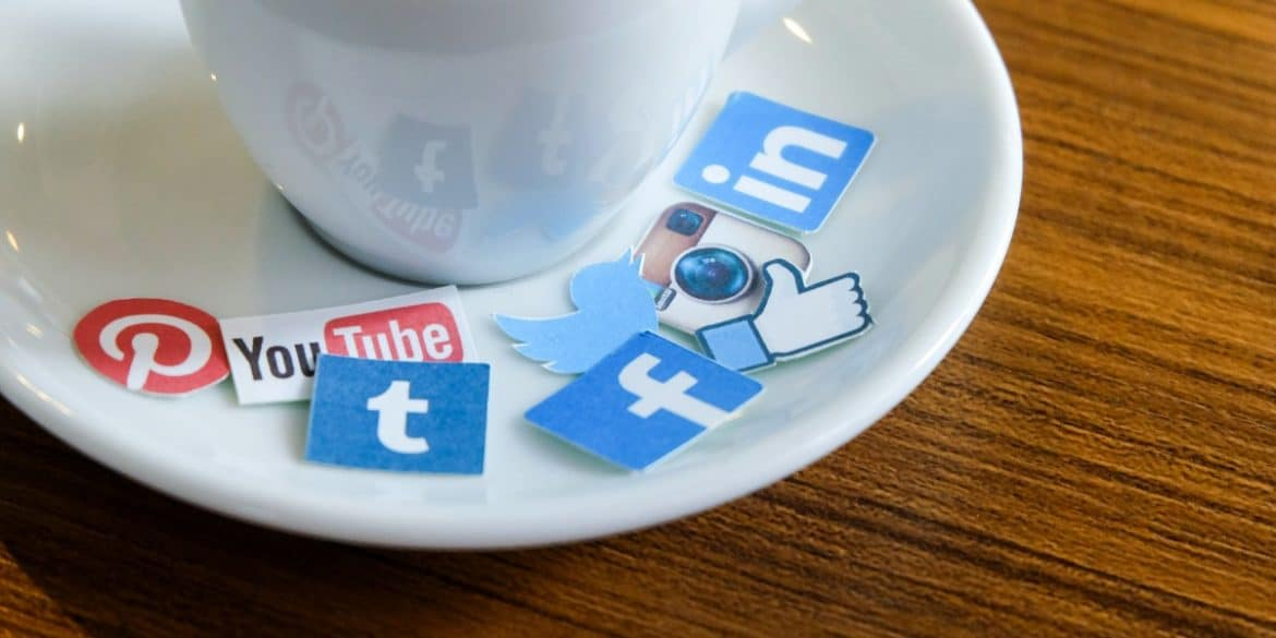 social media stickers on saucer next to coffee cup
