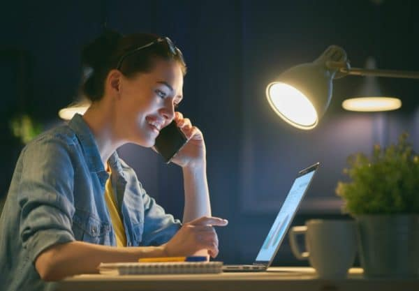 Woman working on laptop while talking on a mobile phone